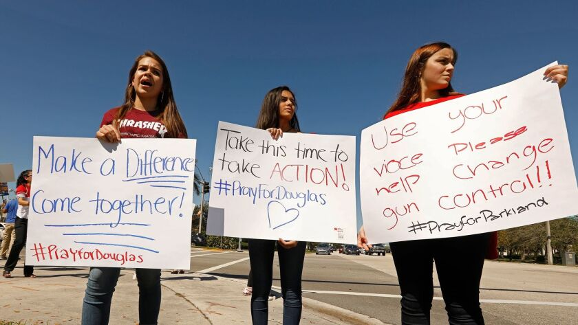 Young protesters gather Feb. 16 on a corner near Marjory Stoneman Douglas High School in Parkland, Fla., to call for gun control after a gunman killed 17 and injured 14.
