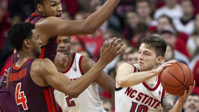 North Carolina State's Braxton Beverly (10) is trapped by Virginia Tech's Nickeil Alexander-Walker (