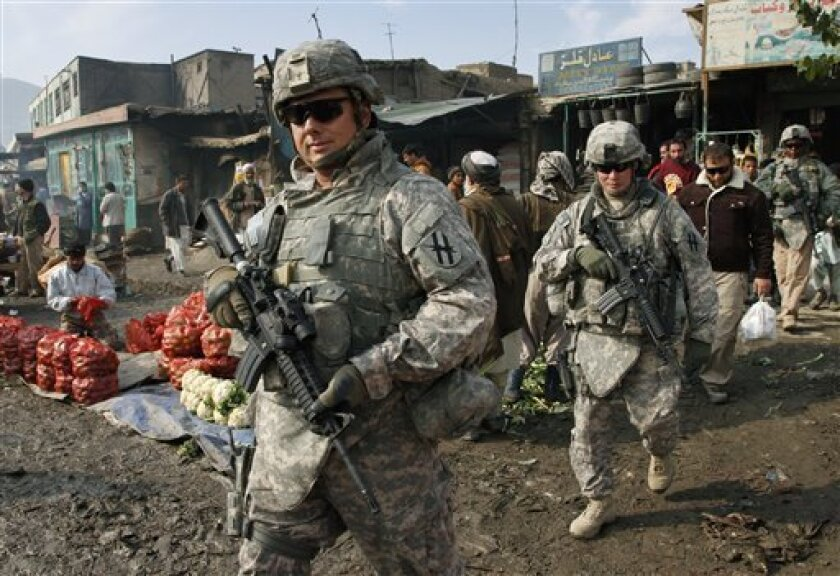 "U.S. soldiers patrol through the heart of Kabul, Afghanistan on Wednesday, Dec. 2, 2009. Many Afghans were still sleeping when President Barack Obama announced he was sending 30,000 more U.S. troops to the war. Gen. Stanley McChrystal, the top U.S. commander in Afghanistan, said NATO and U.S. forces would hand over responsibility for securing the country to the Afghan security forces ""as rapidly as conditions allow."" Obama said if conditions are right, U.S. troops could begin leaving Afghanistan in 18 months. (AP Photo/Musadeq Sadeq)"