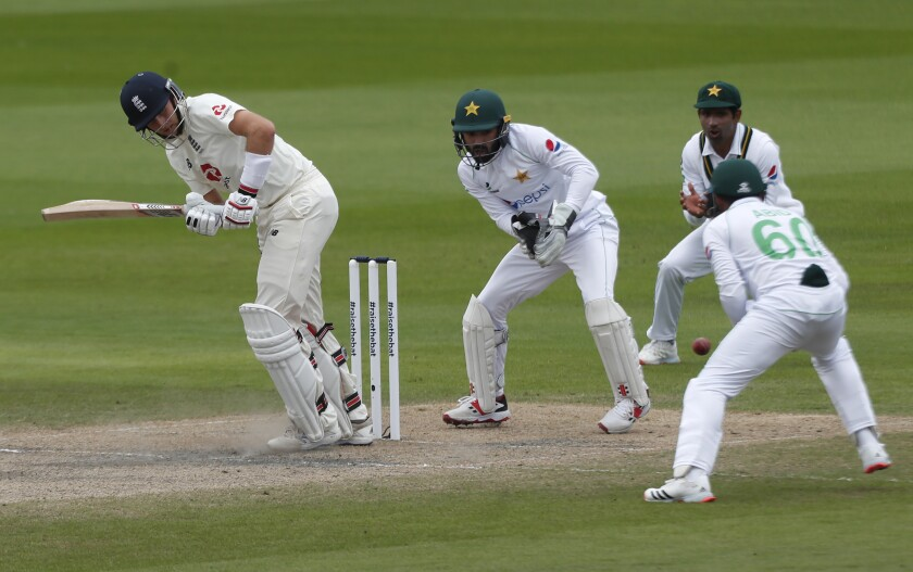 England's captain Joe Root, left, plays a shot during the fourth day of the first cricket Test match between England and Pakistan at Old Trafford in Manchester, England, Saturday, Aug. 8, 2020. (Lee Smith/Pool via AP)