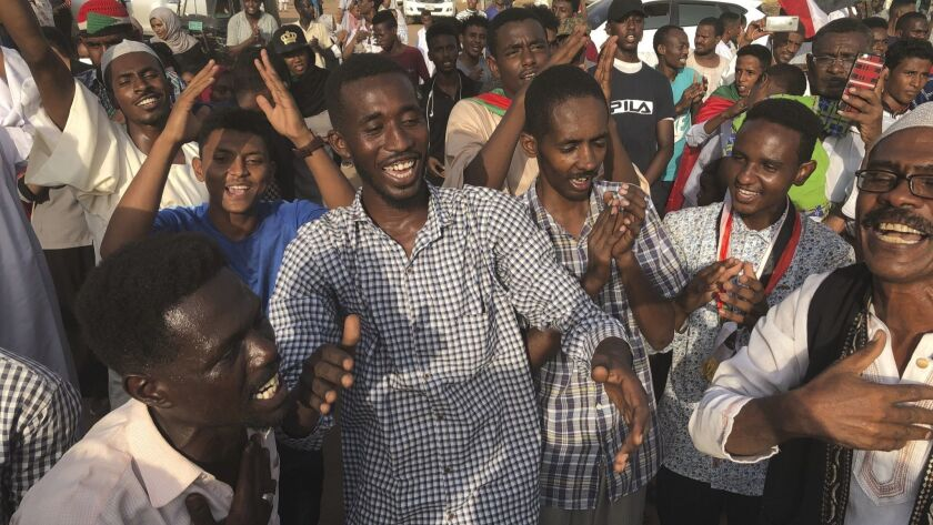 Sudanese people celebrate in the streets of Khartoum after ruling generals and protest leaders announced they had reached an agreement on the disputed issue of a new governing body on Friday.