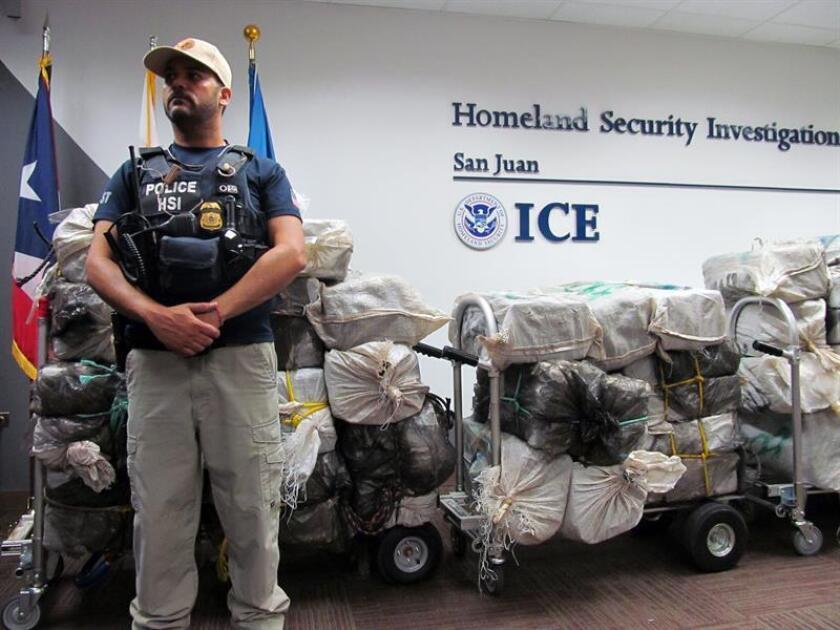 Un agente de la Agencia de Aduanas y Protección Fronteriza (ICE) custodia unos bultos que contienen kilos de cocaína durante su presentación en una rueda de prensa. EFE/Archivo