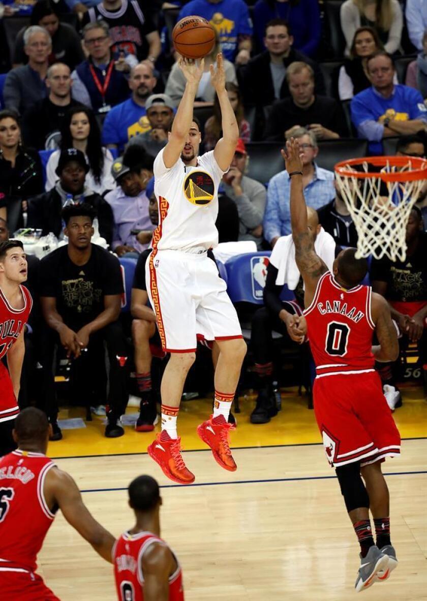 Klay Thompson (c) de Golden State Warriors lanza sobre Isaiah Canaan (d) de Chicago Bulls en un juego de la NBA en Oracle Arena en Oakland (EE.UU.). EFE