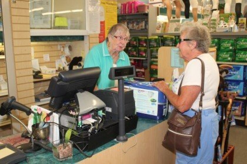 Burns Drugs' clerk Grace 'Betty' Clifford assists customer Jo Nerini. Oct. 25 was Clifford's last day before retiring.
