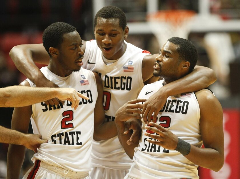 LtoR Xavier Thames, Skylar Spencer and Chase Tapley take in the win as time winds down in overtime. Aztecs went on to beat CSU 79-72.