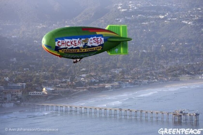 """Greenpeace campaigners said they are trying to convince San Diego-based Chicken of the Sea to kill fewer non-tuna species by flying a colorful airship off the coast of La Jolla this week. Industry leaders said the international activist group is operating a misguided publicity stunt rather than seeking """"meaningful collaboration."""""""