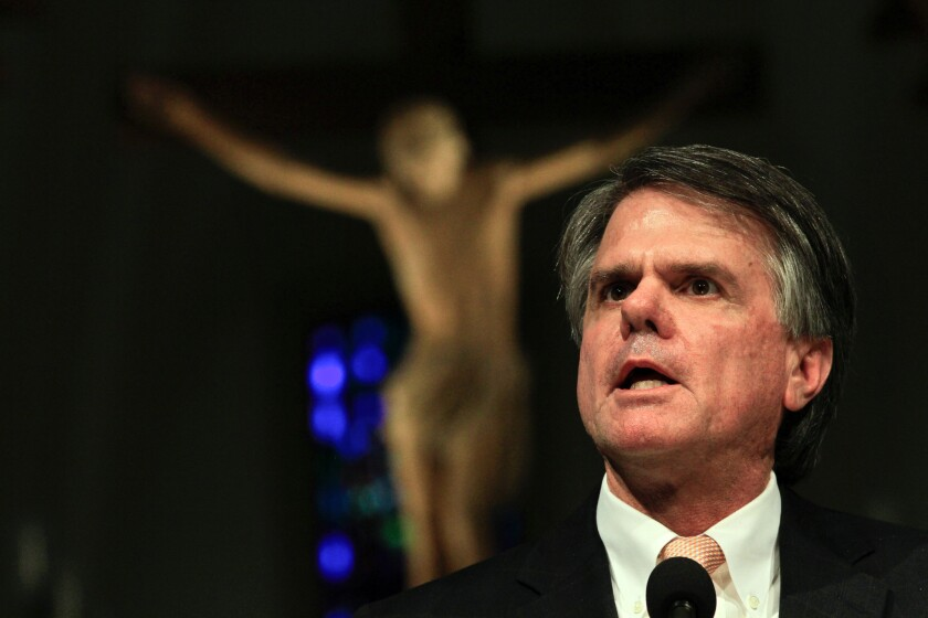 Loyola Marymount University President David W. Burcham, here speaking at a campus chapel, is resigning in May after five years in the post.