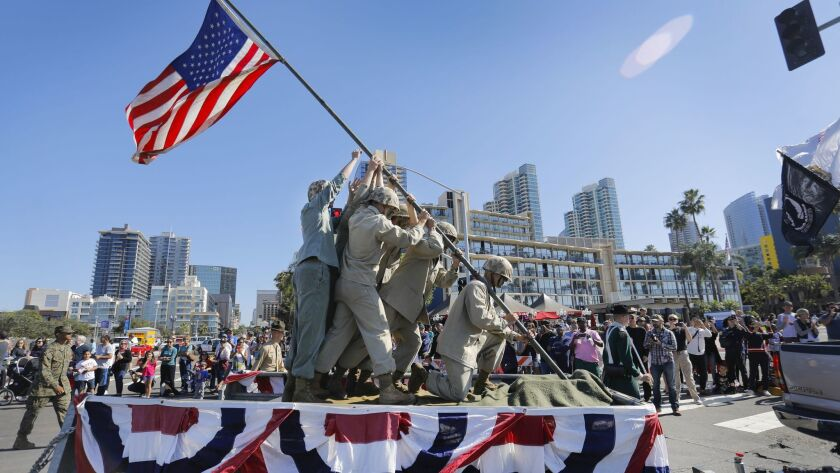 Members of the Marine Corps ride on the West Coast Drill Instructor Association float as they reenact the iconic World War II raising of the American flag on Iwo Jima, during the 2017 San Diego Veterans Day Parade along Harbor Drive.