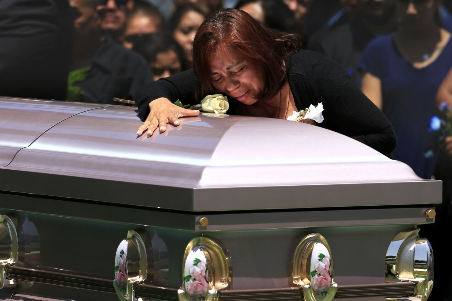 Macrina Reyes cries while she places a flower on the coffin of her transgender daughter, Zoraida Reyes, 28, during graveside services at Santa Ana Cemetery on June 23.