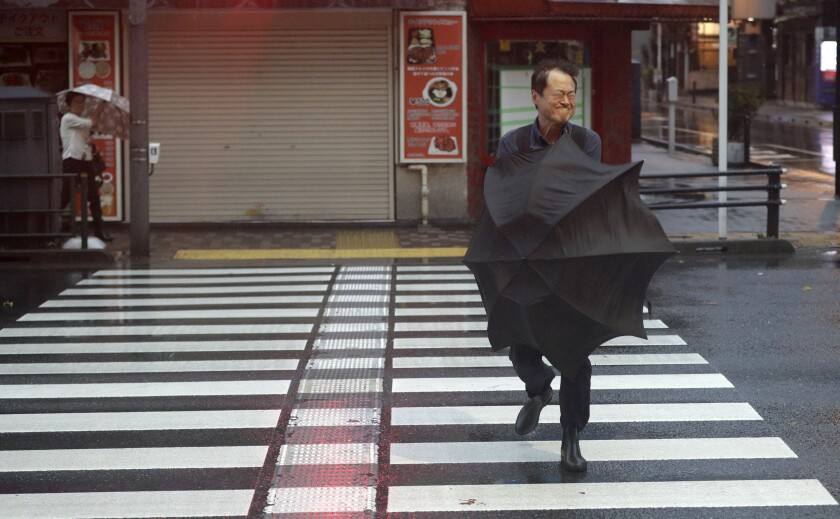 A man battles with his umbrella as he crosses the road in Otemachi district of Tokyo, Japan, Saturday, Oct. 12, 2019. A heavy downpour and strong winds pounded Tokyo and surrounding areas on Saturday as a powerful typhoon forecast as the worst in six decades approached landfall, with streets and train stations deserted and shops shuttered. (AP Photo/Mark Baker)