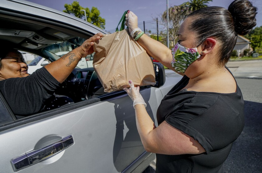 San Diego City Councilmember Vivian Moreno distributes bags of food and hygiene products to a woman during a food drive at Albert Einstein Academies on Saturday.