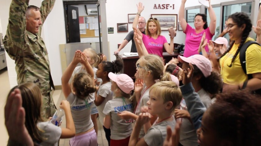 "Project Scientist participants raise their hands during an ""expedition"" to see Black Hawk and Chinook helicopters last summer in St. Paul, Minn. The organization works with girls ages 4 to 12 who are interested in science, technology, engineering and math."
