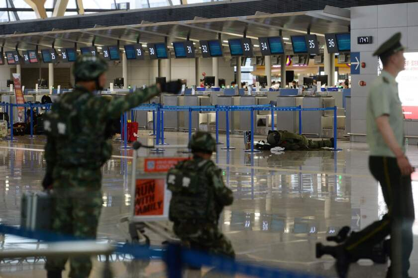 A paramilitary bomb disposal expert (background, right) inspects luggage left near a check-in counter after an explosion at Pudong Airport in Shanghai on Sunday.