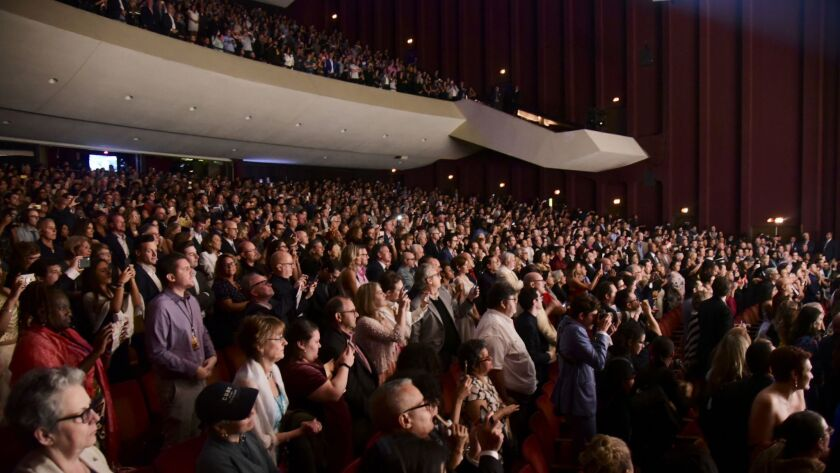 The audience attending the award-winning Broadway musical, Hamilton, gives a standing ovation at the