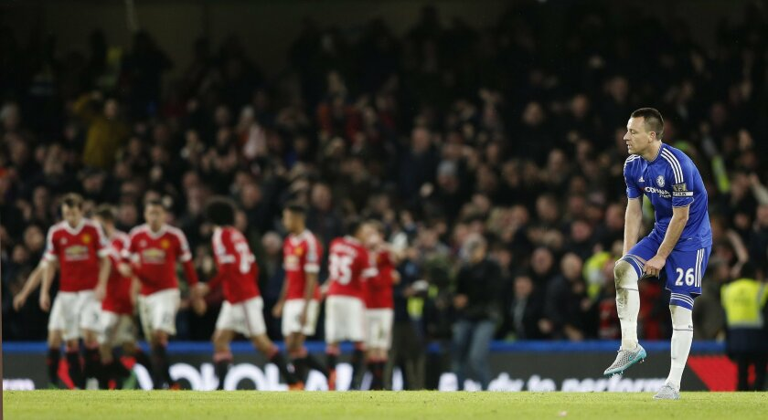 Chelsea's John Terry reacts as Manchester United players celebrate after Jesse Lingard scored the opening goal during the English Premier League soccer match between Chelsea and Manchester United at Stamford Bridge stadium in London, Sunday, Feb. 7, 2016.  (AP Photo/Frank Augstein)