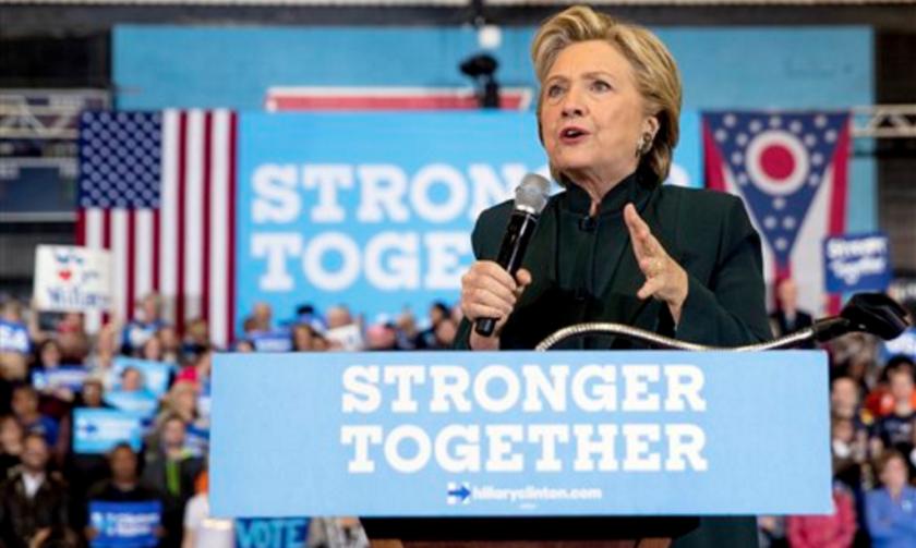 """Hillary Clinton habla en un acto en Cleveland, en un escenario decorado con carteles que dicen """"Juntos somos más fuertes"""". La candidata demócrata a la presidencia no tiene demasiadas esperanzas de ganar un estado típicamente republicano como Texas, pero ha repuntado en las encuestas y tiene preocupados a los republicanos, para quienes un revés en ese bastión sería catastrófico. (AP Photo/Andrew Harnik, File)"""