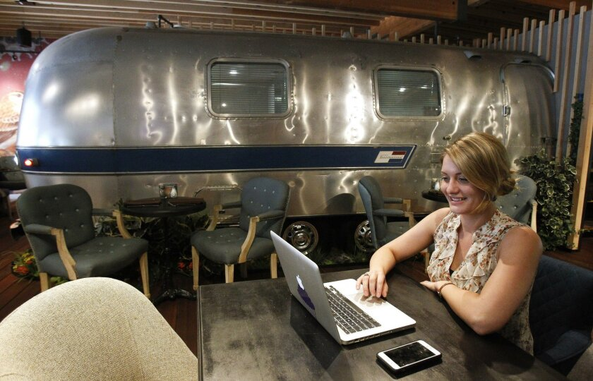 The general manager for the Farmer & Seahorse restaurant uses a computer while sitting near a travel trailer that's converted into a private dining room at Alexandria Real Estate's $25 million restaurant, gym, and conference center in Torrey Pines Mesa.