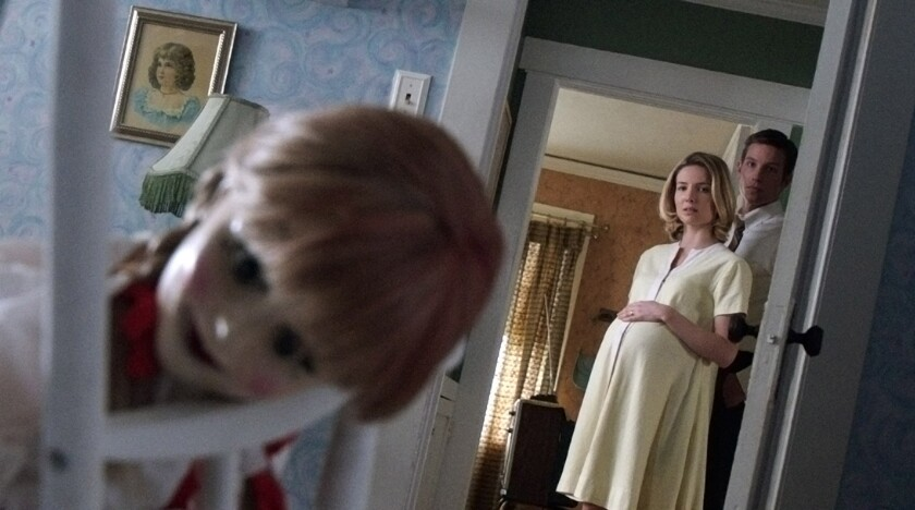 """Annabelle Wallis, left, as Mia and Ward Horton as John with the Annabelle doll in the thriller """"Annabelle."""""""