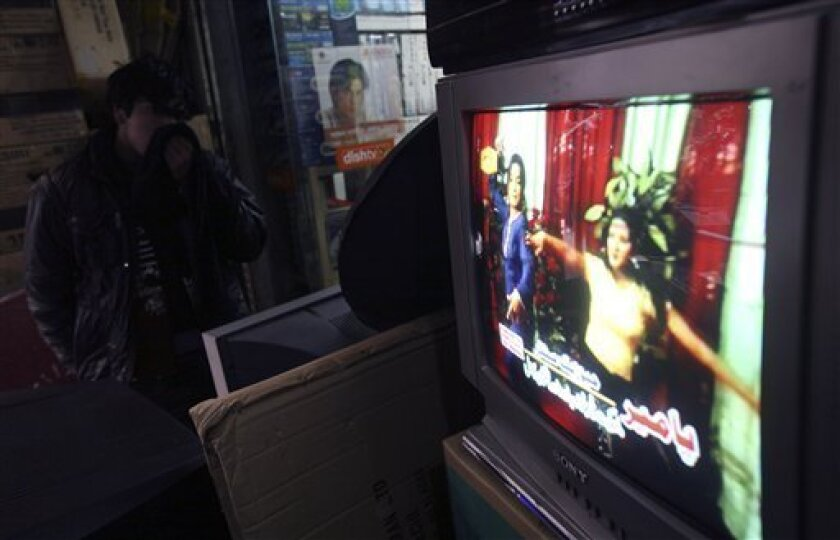An Afghan youth watches televisions displayed for sale, showing dancing women on screen at a TV shop in Kabul, Afghanistan on Thursday Jan. 22, 2009. Television has flourished in Afghanistan since the hard-line Taliban regime was ousted in 2001. Eleven private stations and one state channel now bro