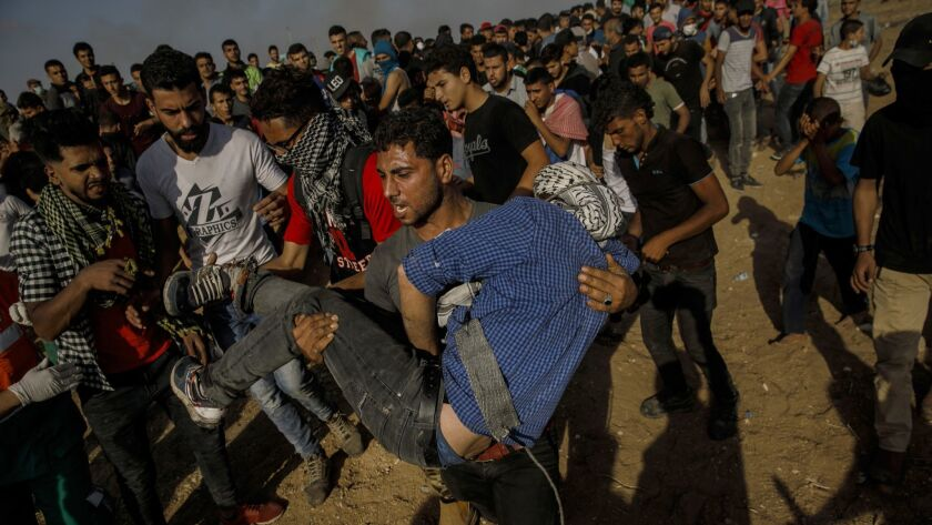 GAZA CITY, GAZA STRIP -- FRIDAY, MAY 11, 2018: A Palestinian man carry a fellow protester out after