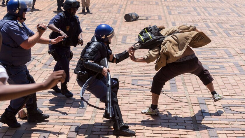 A police officer grabs a student on campus at the University of Witwatersrand in Johannesburg.