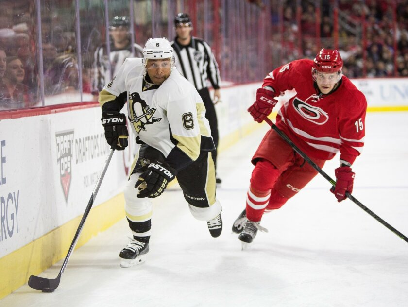 Pittsburgh Penguins' Trevor Daley (6) handles the puck as Carolina Hurricanes' Andrej Nestrasil (15), of Czech Republic, trails during the first period of an NHL hockey game in Raleigh, N.C., Friday, Feb. 12, 2016. (AP Photo/Ben McKeown)