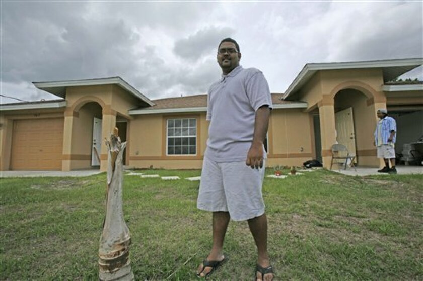 In this  May 19, 2009 photo, Mike Manikchand, a 22-year-old pharmacy student, poses in front his duplex in Lehigh Acres, Fla. Manikchand  took advantage of the dismal housing market and bought the foreclosed duplex for a low price but now, looking at the empty house around him, he wonders what will