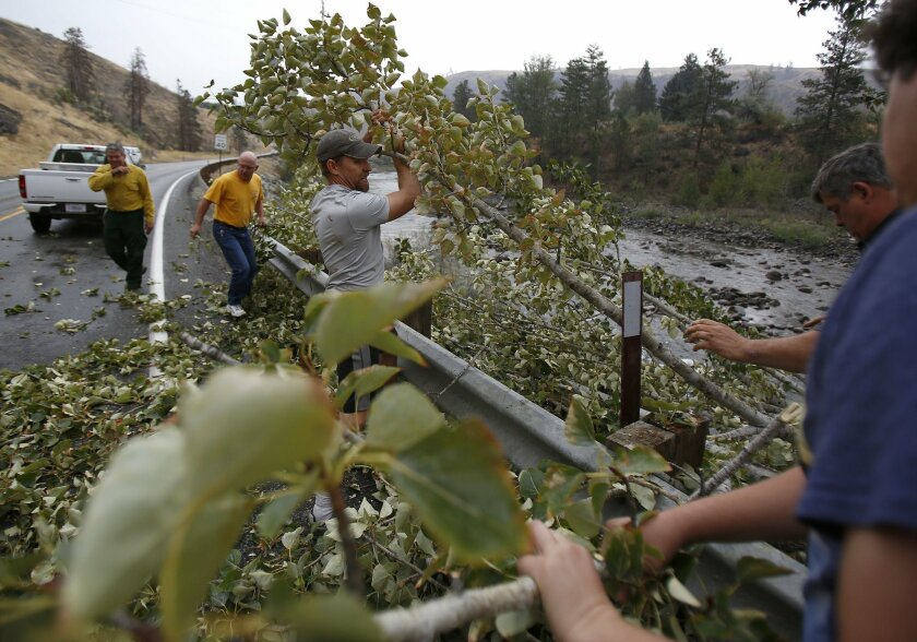 Jason Getzin, center, pastor at the Calvary Chapel Association in Twisp, Wash., helps remove debris after a high winds and light rain brought down part of a tree across state Route 153, Saturday, Aug. 29, 2015, in the Methow Valley outside Methow, Wash. Powerful winds toppled trees and power lines across the Pacific Northwest on Saturday, causing at least two deaths in the Seattle area and knocking out electricity to at least a quarter-million customers in Oregon and Washington. (Sy Bean/The Seattle Times via AP) SEATTLE OUT; USA TODAY OUT; MAGS OUT; TELEVISION OUT; NO SALES; MANDATORY CREDIT TO BOTH THE SEATTLE TIMES AND THE PHOTOGRAPHER