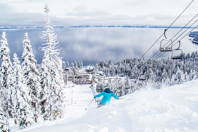 A skier descends a powdery slope at Homewood Mountain Resort with Lake Tahoe below.