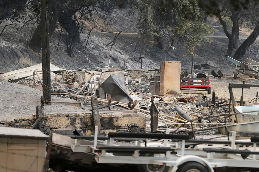 The remains of a structure and boats scorched by the Whittier fire sit along State Route 154 in Los