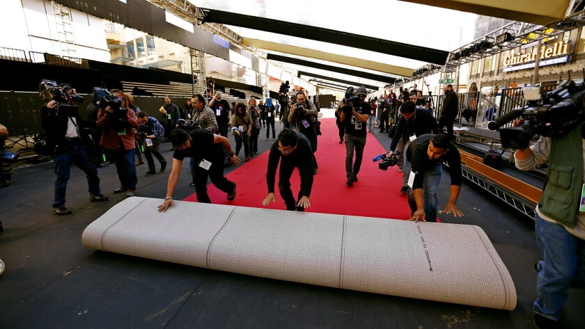 Installers maneuver a red carpet roll in front of the Dolby Theatre.