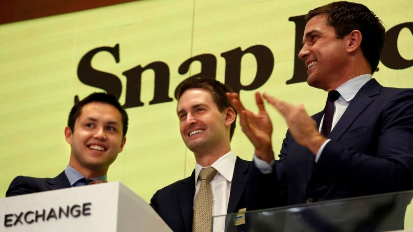 Snap CEO Evan Spiegel, center, and Chief Technology Officer Bobby Murphy, left, ring the bell at the New York Stock Exchange in March.