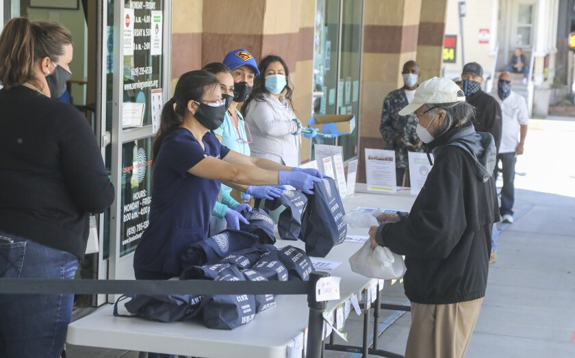 Seniors line up at the Gary & Mary West Senior Wellness Center in downtown to receive dental hygiene kits from the Senior Dental Center on May 22, 2020 in San Diego, California.