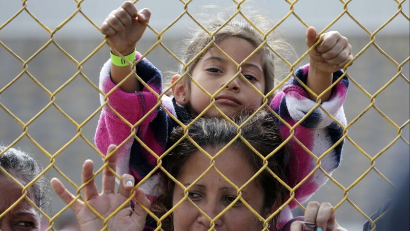 A six-year-old sits on the shoulders of her mother as they look out through the fence of a immigrant shelter in Piedras Negras, Mexico on Feb. 5.