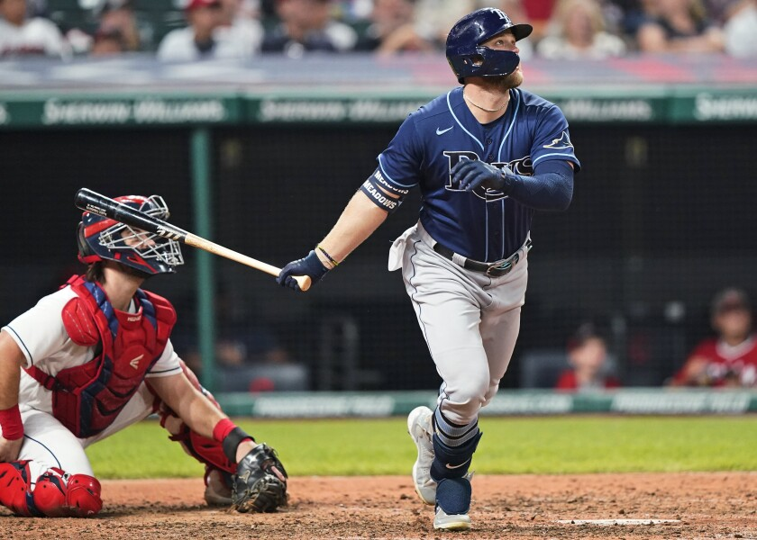 Tampa Bay Rays' Austin Meadows watches his two-run home run next to Cleveland Indians catcher Austin Hedges in the ninth inning of a baseball game Saturday, July 24, 2021, in Cleveland. (AP Photo/Tony Dejak)
