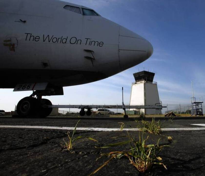A FedEx plane is parked in front of Riverside Municipal Airport's air-traffic control tower, which is among those set to close next month.