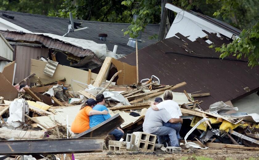 Miembros de la familia Cisco se consuelan durante un descanso en las tareas de búsqueda entre los escombros.