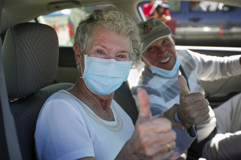 A husband and wife sit in their car and give a thumbs-up after receiving the first dose of the COVID-19 vaccine