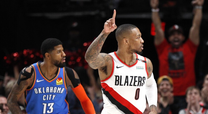 Portland Trail Blazers guard Damian Lillard, right, reacts after making a basket as Oklahoma City Th