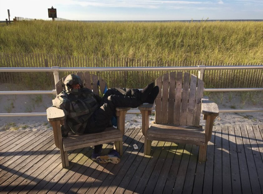 A man sleeps on a Boardwalk bench in Atlantic City, New Jersey.