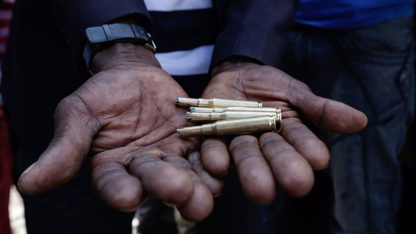 A Kenyan opposition supporter holds spent bullet cartridges allegedly fired by police to quell protests and rioting after a disputed election.