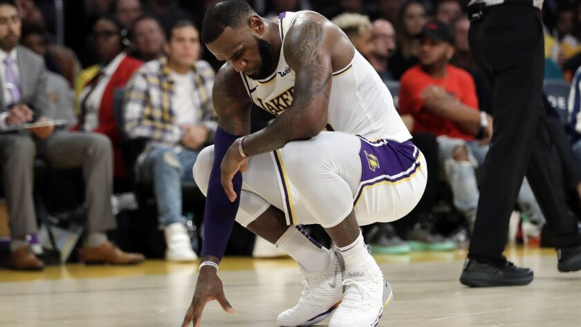Lakers' LeBron James kneels after a foul is called against the Lakers during the second half against the Toronto Raptors on Sunday.