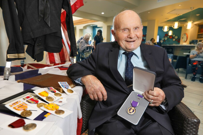 George Coburn holds his Purple Heart Medal with his many other medals, at lower left, he finally received that he earned for his military duty in World War II. U.S. Congressman Mike Levin gave them to him here at Fairwinds Ivey Ranch retirement community