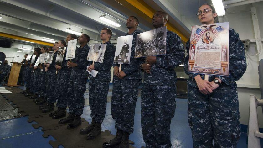 130212-N-DI878-062 PACIFIC OCEAN (Feb. 12, 2013) Sailors hold photos of civil rights activists, arm