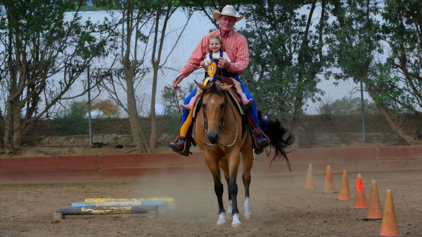 """Lou Roper takes Ivy Fondots for a ride on """"Doc"""" at his horse ranch in San Marcos."""