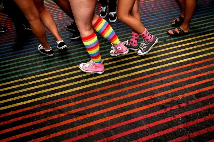 A woman wearing rainbow-colored socks walks across a rainbow-colored crosswalk.