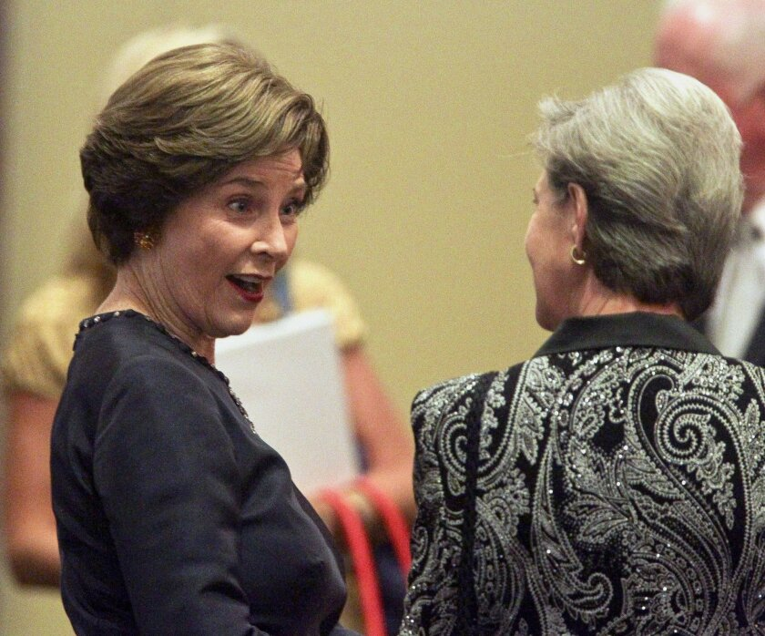 Former First Lady Laura Bush, left, mingles with people after arriving at An Evening to Remember...with Mrs. Laura Bush, a fundraiser for Solutions for Change, at the La Costa Resort and Spa in Carlsbad on Saturday.