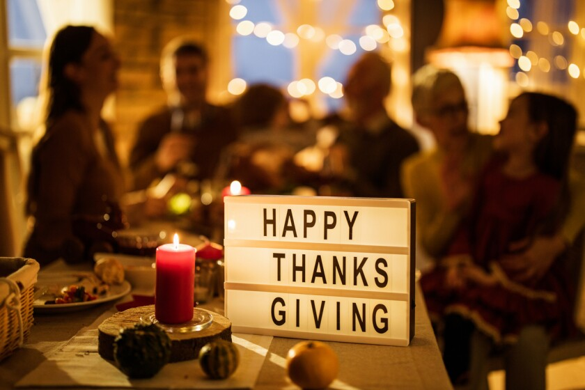 A sign with 'Happy Thanksgiving' on dining table with people in the background.