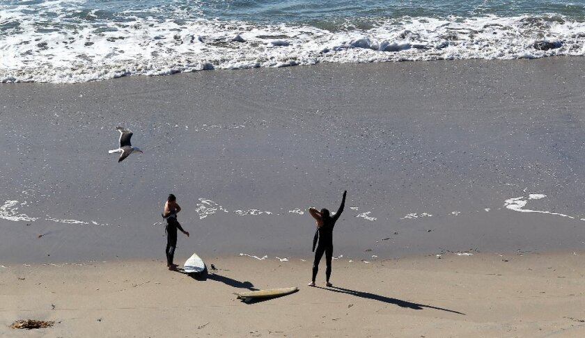 Surfers put on their wetsuits before entering the water at Powerhouse Park in Del Mar.