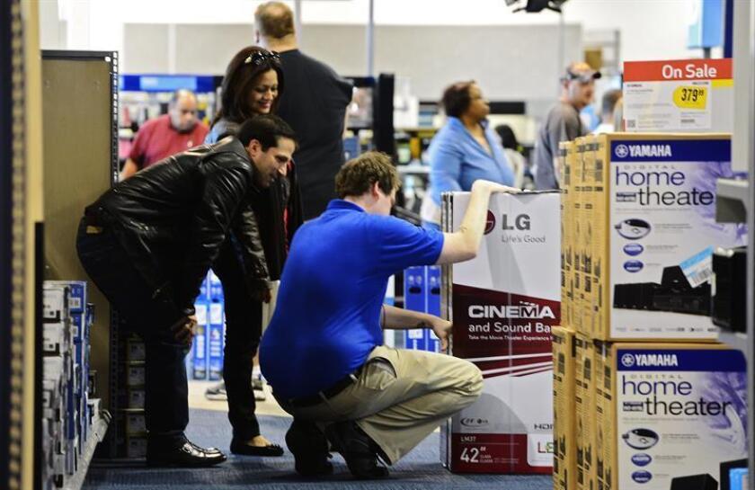 Una pareja recibe ayuda de un dependiente mientras van de compras. EFE/Archivo